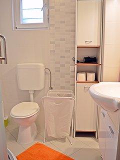 Bathroom with shower, toilet, washbasin and bathroom closet.