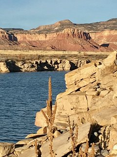 Abiquiu Lake, surrounded by red rock formations, just below the home.