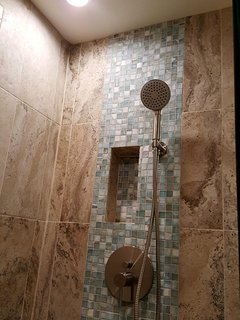 Walk-in Shower with shampoo nook and shower wand.
