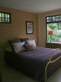 Master bedroom with queen bed and view to back patio