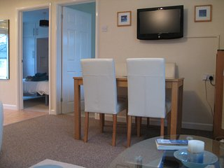 Dining area, table for4 TV.DVD player, DVDs, guide books, maps.  Doors to bedrooms. Kitchen on left.