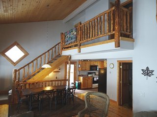Rustic log railing and pine finishes throughout.