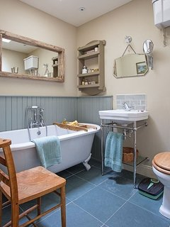 Family bathroom with roll top bath and shower attachment. Basin and WC.