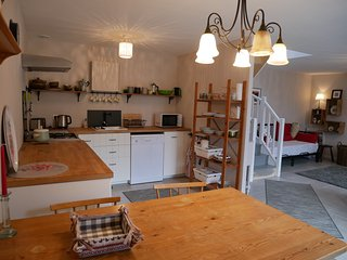Modern kitchen, including dishwasher. Large pine dining table.