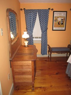 The country antique chest of drawers and mirror fit in with the character of this room.