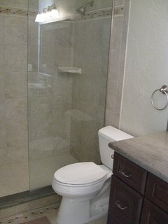 MBR bath with luxury custom tiled shower and fixed glass divider.