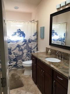 Large guest bathroom with granite countertop, travertine tiles and skylight