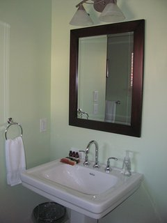 Main level in suite guest  full bathroom with pedestal sink