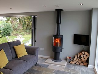 A deep corner sofa with wall-mounted TV and woodburner at one end of the room