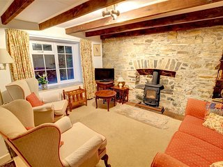The delightful sitting room has plenty of character with a beamed ceiling, stone walls and a woodburner