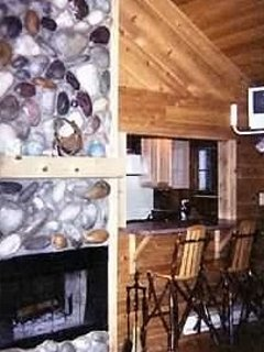 cabin living room with a two way fireplace.  Bar opens to the kitchen.