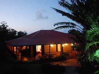 Vue extérieure de la villa dans un écrin de nature tropicale luxuriante