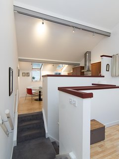 the staircase separates the kitchen and living areas