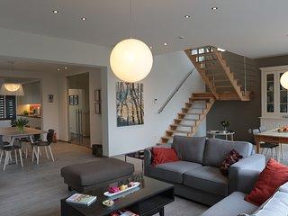 Grote leefruimte met volledig uitgeruste keuken, eethoek, zithoek en leesruimte.