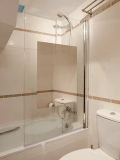 The bathroom on the second floor includes a small bathtub, shower, and well-illuminated mirrors.
