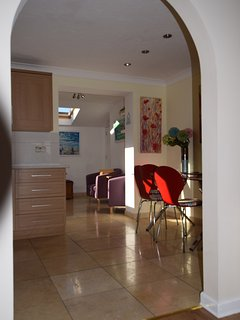 Open plan throughout the downstairs. Decorated with Pete Caswell's colourful local paintings.