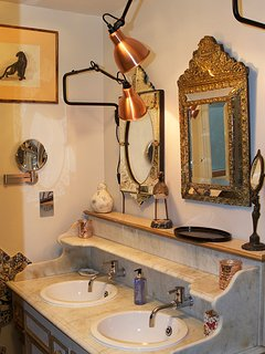 In the bathroom a refurbished mid 19th vanity unit and old Murano and Napoleon III mirrors