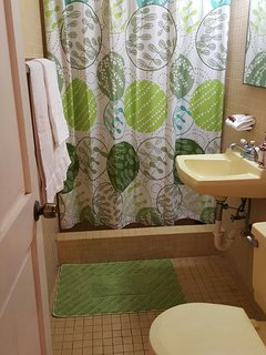 A clean and neat private bathroom with shower is a short step into the hallway.