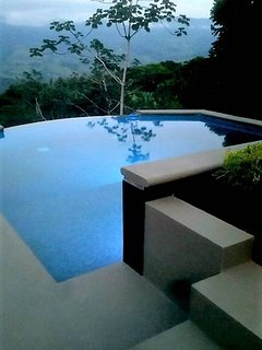 The Steinway Infinity Pool with beach entry amd waterfall at dusk