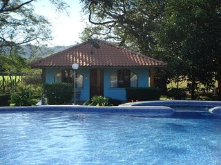 2 bedroom house with communal pool in lush tropical garden