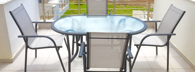 Table with chairs in the balcony with view of the pool