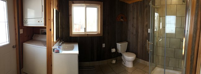 Bathroom overview featuring laundry washer, dryer, vanity, toilet, shower.