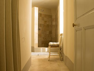 Marble en-suite bathroom with oversized shower, heated towel rail, lit make-up mirror, WC