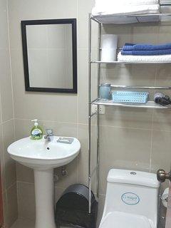 parte del baño, lavatorio, espejo, articulos de aseo, al costado està la ducha.