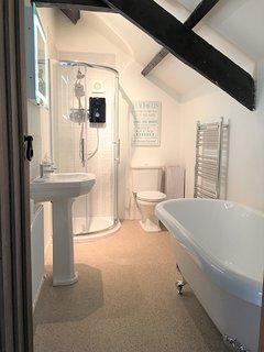 Newly fitted bathroom with roll-top bath and free-standing shower