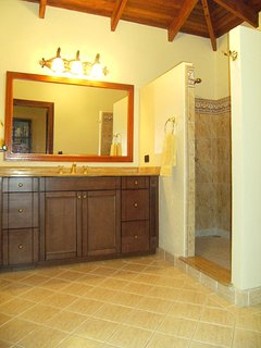 All bathrooms feature large walk-in showers with designer tiles, custom cabinets and marble tops.