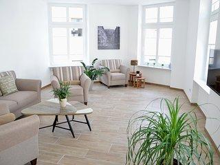 Schöner heller Wohnraum mit gemütlicher Sitzgruppe und Flachbild-TV.