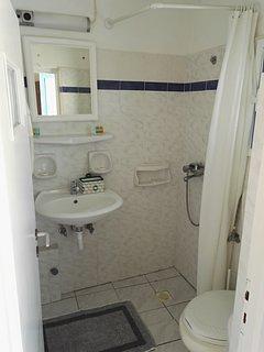 Une salle de bain privative avec douche, sèche-cheveux  et produits de soins
