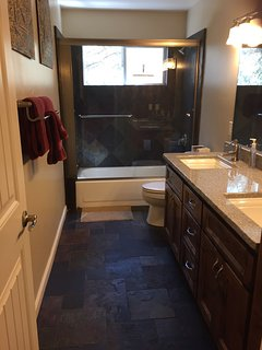 Downstairs bathroom. Dual sinks. Slate tub/shower.