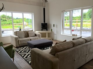 Comfortable living room area with great light, views of the gardens and a cozy wood burning stove.