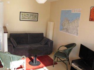 Coin salon avec canapé lit neuf et confortable, TV, chaine hi-fi et livres sur Bretagne et voile
