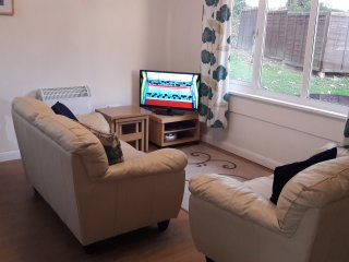 Lounge with laminate floor, leather settees and 32' TV