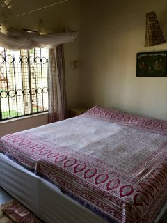 Third bed room with large double bed and mosquito net