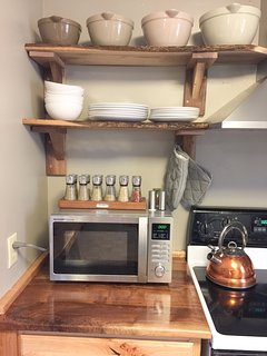The kitchen is stocked with dinnerware for 6, Small appliances coffee maker, toaster and a microwave