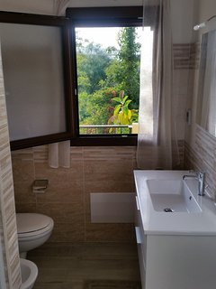 The bathroom is equipped with window and mosquito net, shower and bidet.