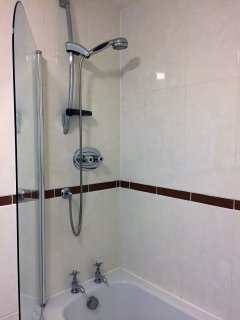 The floor to ceiling tiled bathroom is fitted with a power shower