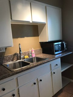 Kitchen sink area and microwave.