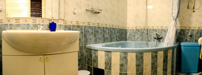 Bathroom comprises: a sink, several wall storage units, toilet & an extra-large bath-tub with shower