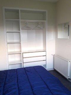 La chambre bleue avec lit 2 personnes en 140x190 et grande armoire-penderie ouverte.