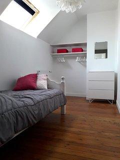 La chambre rose avec lit 1 personne en 90x190, commode et espace penderie ouvert.