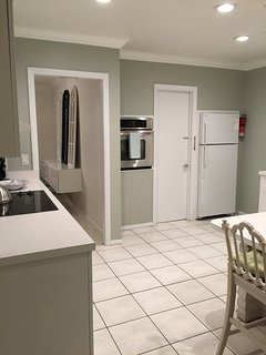Utility room off the kitchen with laundry and storage facilities leading to garage.