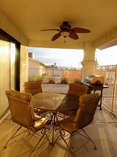 Rear patio ares with table and chairs, also gas BBQ grill and overhead fan.