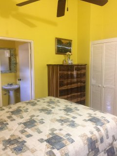 Home Sweet Getaway...back bedroom, chest of drawers and bedside tables and chair, ceiling fan, a/c