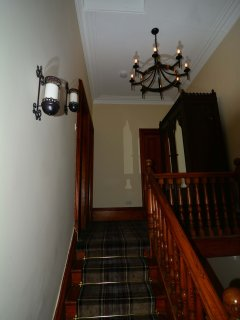 Upper stairwell.  Medeival lighting. Tartan carpeting.