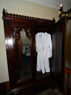 Medeival wardrobe with plush white gowns and slippers for all.