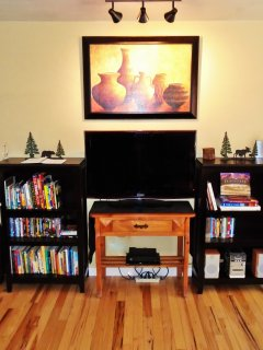 Entertainment area with flat screen TV, cable, books, stereo, DVD player, DVDs.